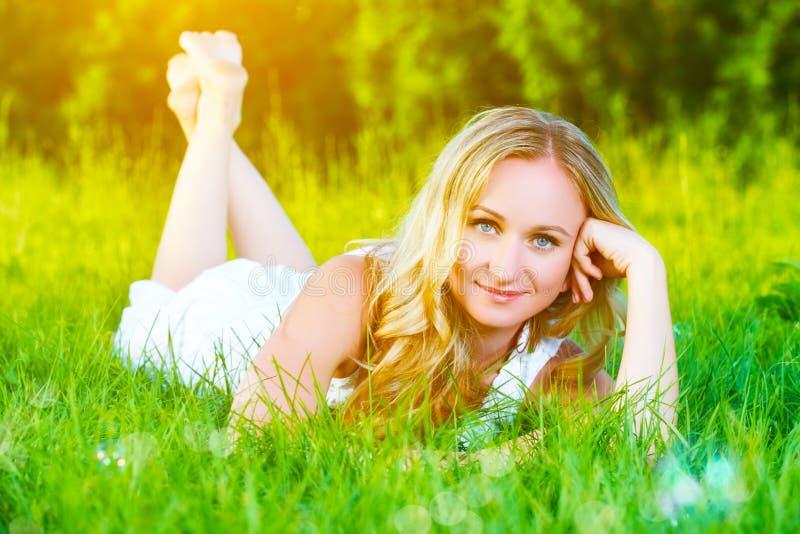 Schöne glückliche träumerische Frau im Sommer auf der Natur, die auf Gras liegt lizenzfreie stockbilder