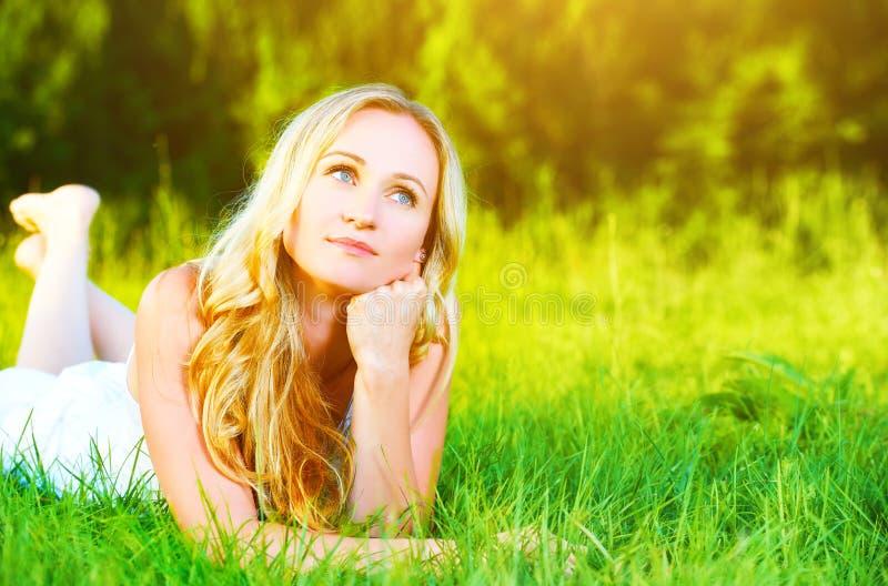 Schöne glückliche träumerische Frau im Sommer auf der Natur, die auf Gras liegt lizenzfreies stockbild