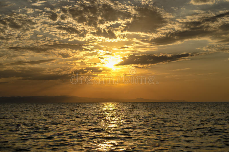 Schöne glühende Sonnenunterganglandschaft am Kaspischen Meer und am orange Himmel über ihr mit goldener Reflexion der ehrfürchtig lizenzfreies stockfoto