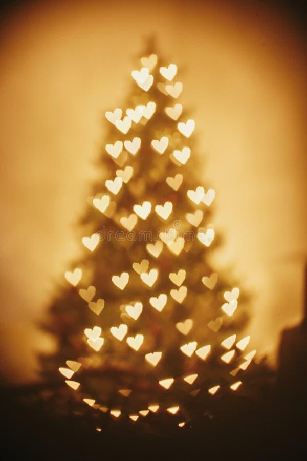 Schöne goldene Lichtherzen des Weihnachtsbaums im festlichen Raum C lizenzfreie stockfotos