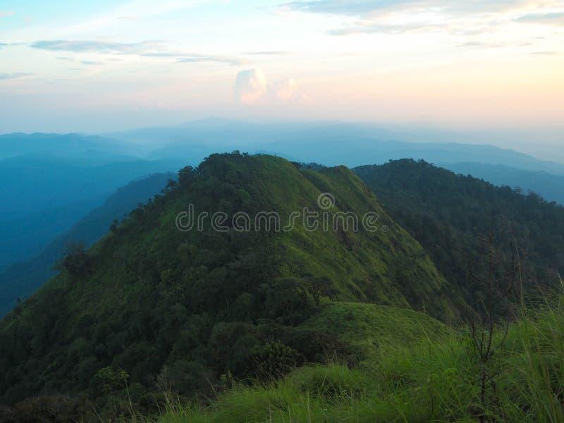 Schöne Grünlandschaft durch Berg und Sonnenunterganghimmel mit Wiese stockfoto