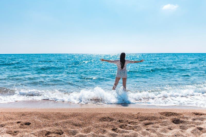 Schöne griechische junge Brünettefrau auf Strand im weißen Kleid stockbild