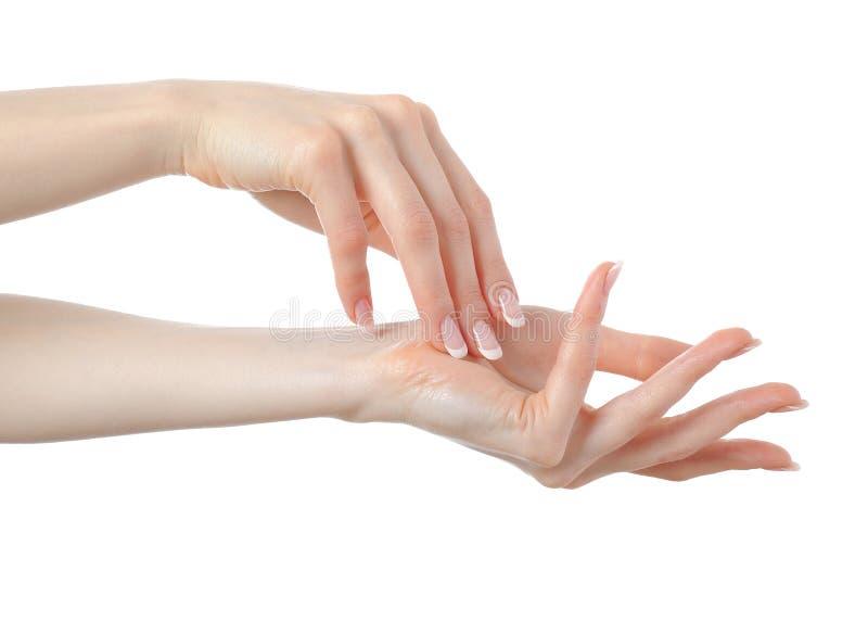 Schöne Hände mit französischer Maniküre des vollkommenen Nagels stockfotografie