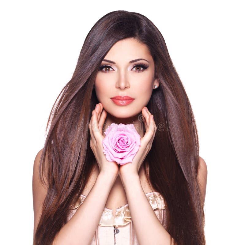 Schöne hübsche Frau mit langer Haar- und Rosarose am Gesicht lizenzfreie stockfotografie