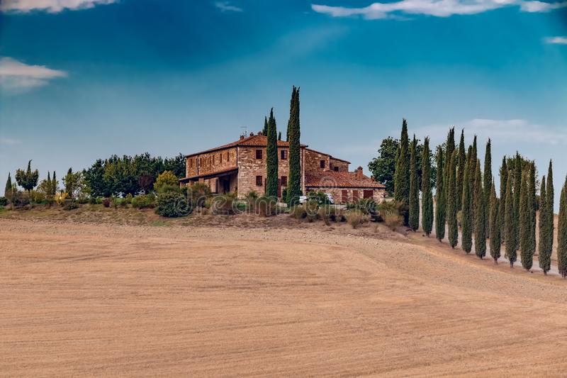 Schöne Hügel mit Gutshaus und Zypressen in Toskana, Italien lizenzfreie stockbilder