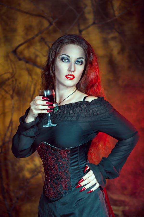 Schöne Halloween-Frau mit Glas Wein lizenzfreies stockbild