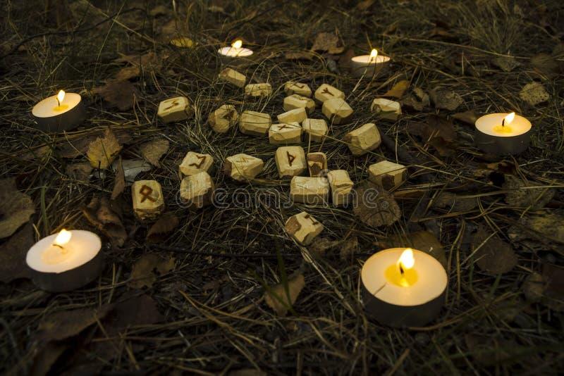 Schöne Halloween-Zusammensetzung mit Runen, dem Schädel, Tarock und Kerzen auf dem Gras im dunklen Herbstwaldritual stockfoto