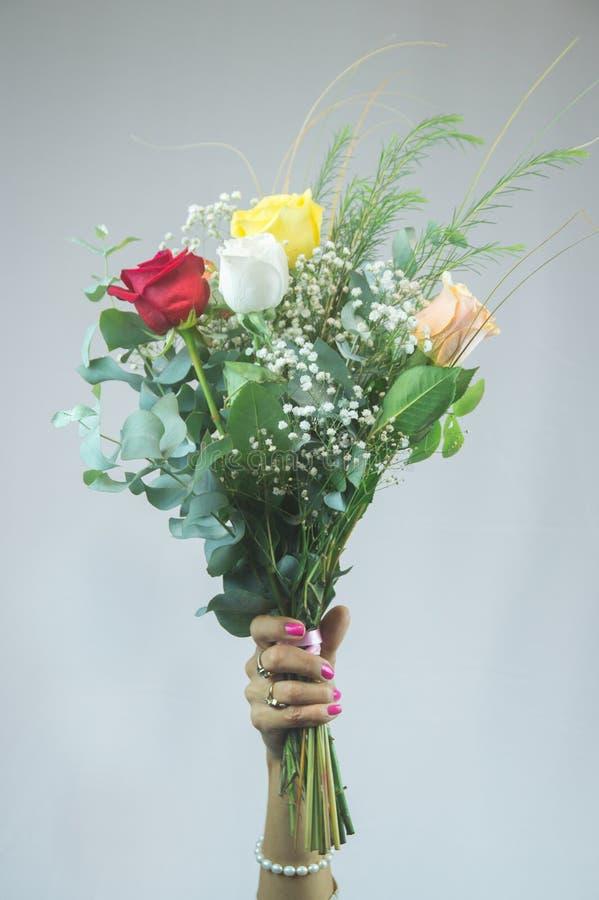 Schöne Hand, die einen Blumenstrauß von Rosen hält stockbild