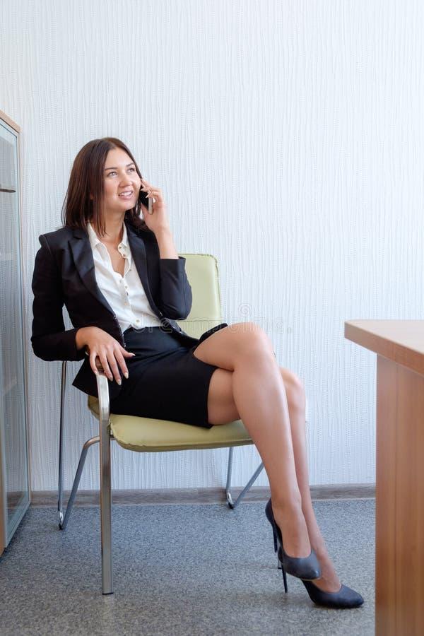 Schöne am Handy sprechende und, auf Stuhl im Büro lächelnde Geschäftsfrau stockfotos