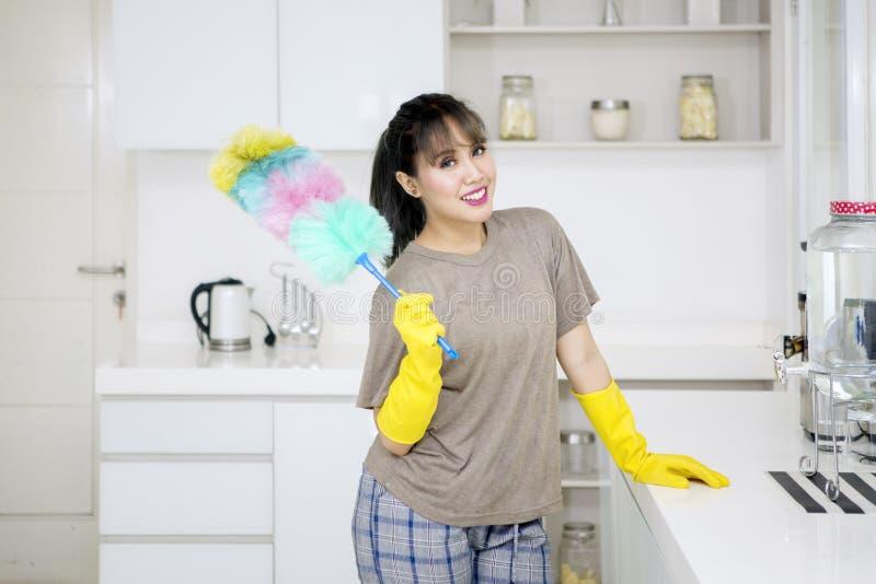 Schöne Hausfrau hält eine Staubtuchbürste zu Hause lizenzfreie stockfotos