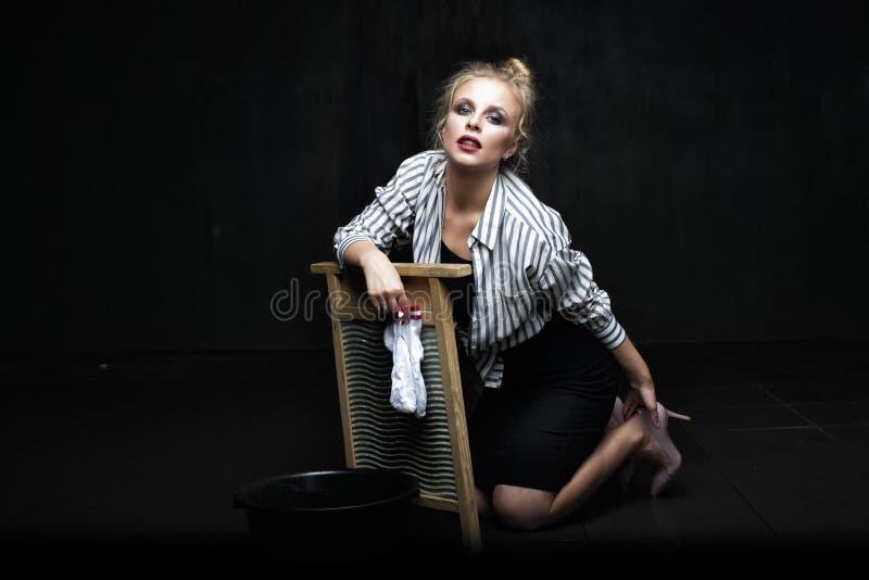 Schöne Hausfraufrau, die Wäscherei tut lizenzfreie stockbilder