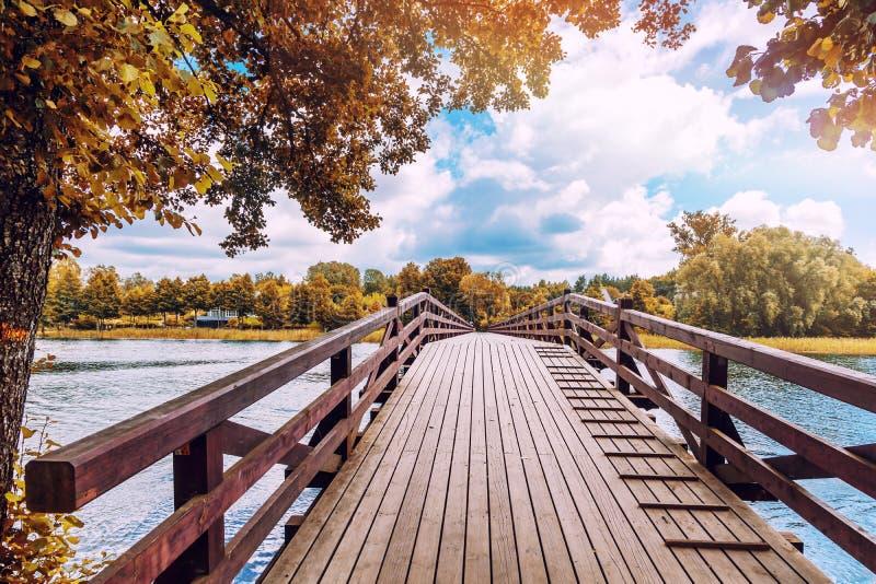 Schöne helle bunte Herbstlandschaft, ein Holzbrücke acro lizenzfreie stockbilder