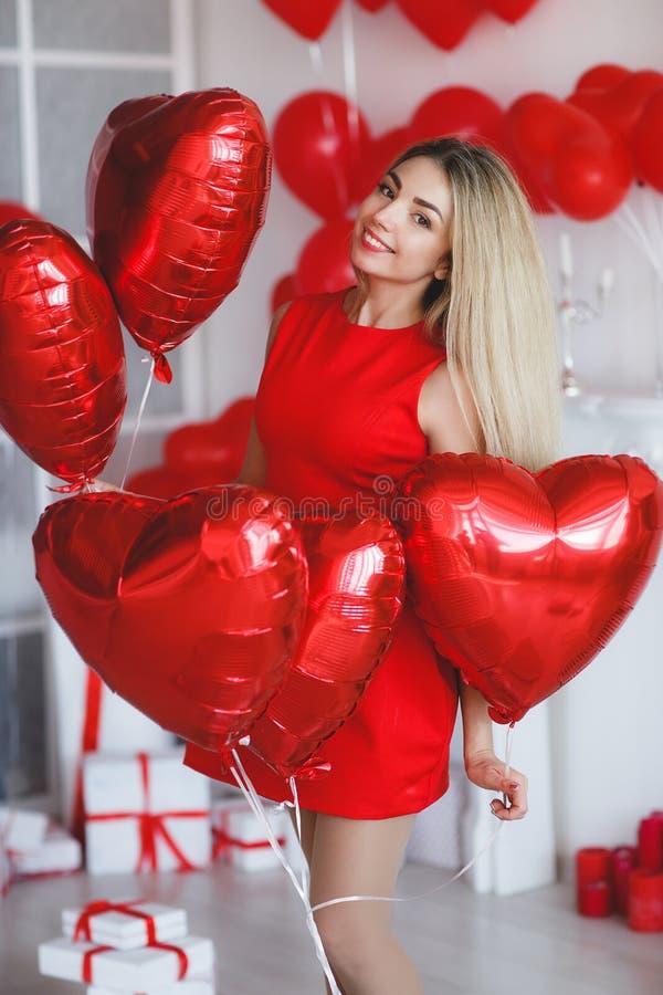 Schöne helle Frau mit roten Ballonen an Valentinsgruß ` s Tag stockfotos