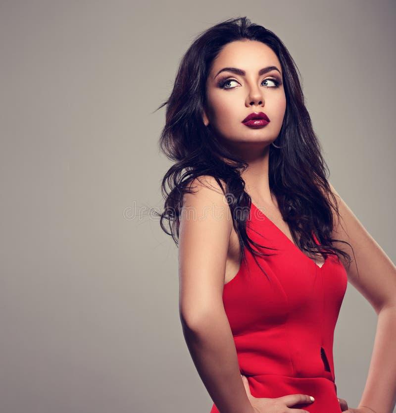 Schöne helle Make-upfrau mit langer schwarzer gelockter Frisur im roten Kleid, Burgunder-Lippenstift mit Vampblick auf grauem Hin lizenzfreies stockfoto