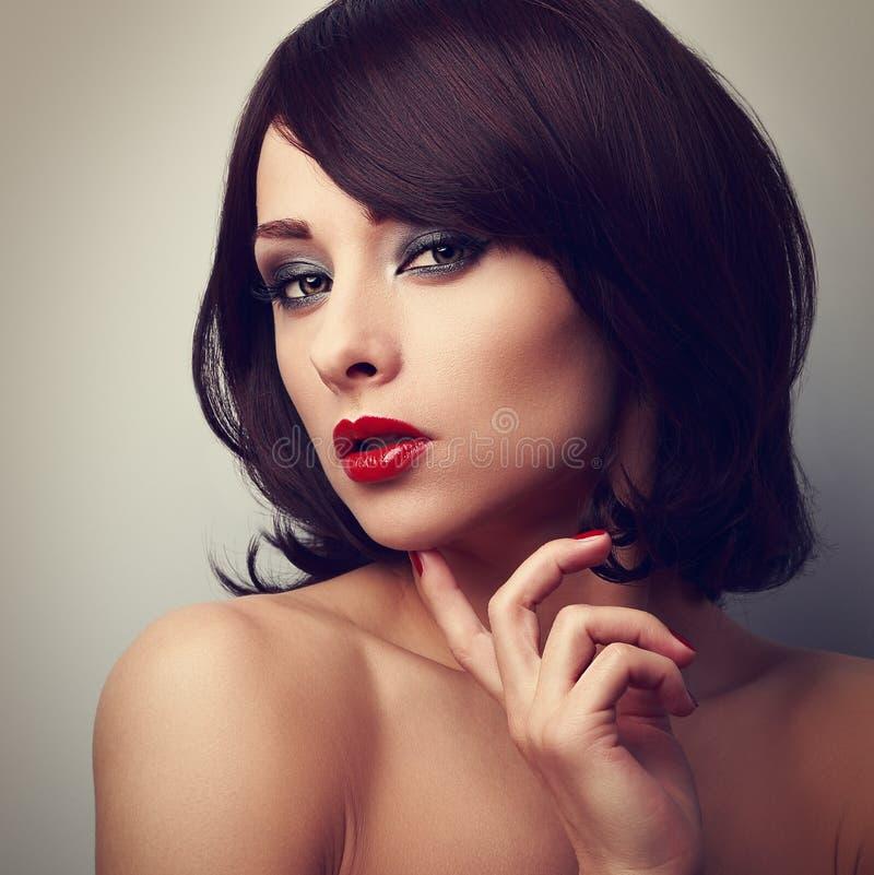Schöne helle Make-upfrau mit rührendem Gesichtsth des roten Lippenstifts stockfoto