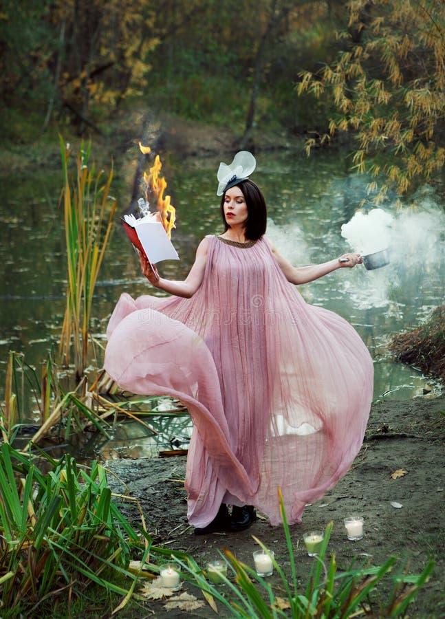 Schöne Hexe auf dem Sumpf, der ein brennendes Buch und einen Zaubertrank hält stockfoto