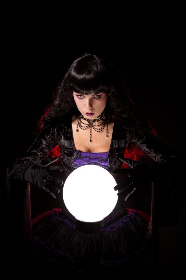 Schöne Hexe oder Wahrsager mit einer Glaskugel lizenzfreie stockfotos