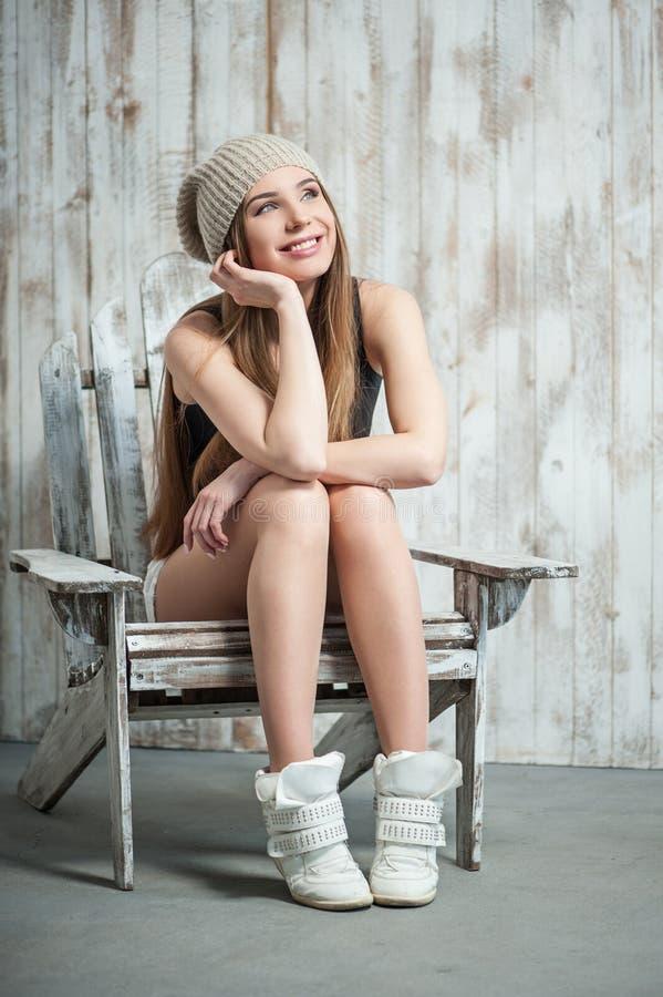Schöne Hippie-Frau sitzt auf dem Stuhl stockfotografie