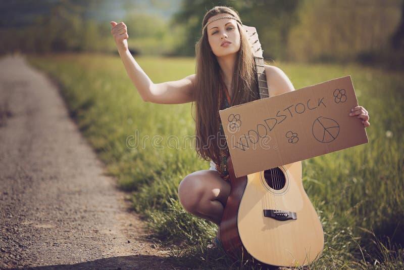 Schöne Hippie mit der per Anhalter fahrenden Gitarre lizenzfreie stockbilder