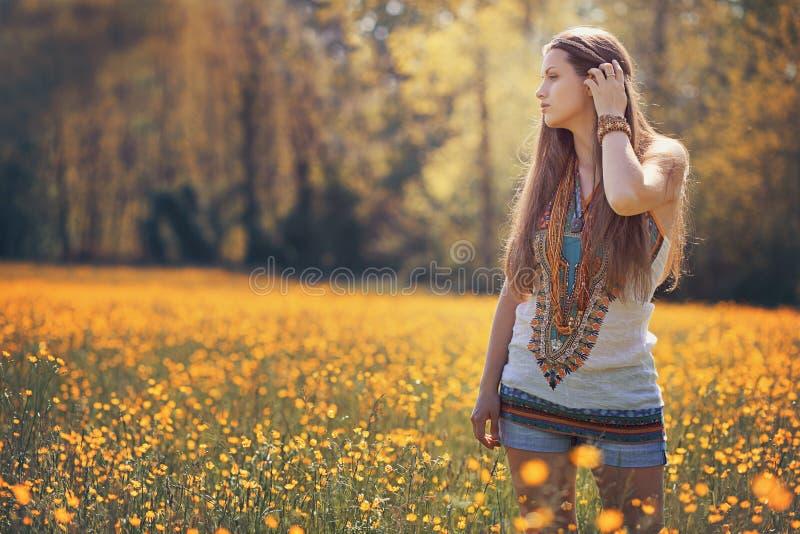 Schöne Hippiefrau auf dem Blumengebiet stockfotos