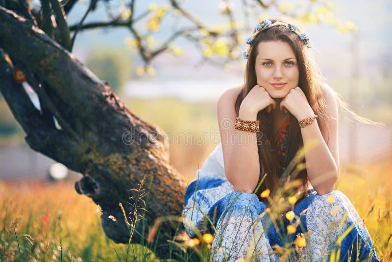 Schöne Hippiefrau, die auf einem Sommergebiet aufwirft lizenzfreie stockbilder