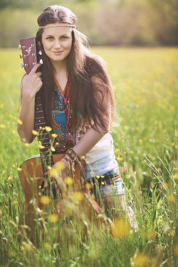 Schöne Hippiefrau, die mit Gitarre aufwirft lizenzfreie stockbilder