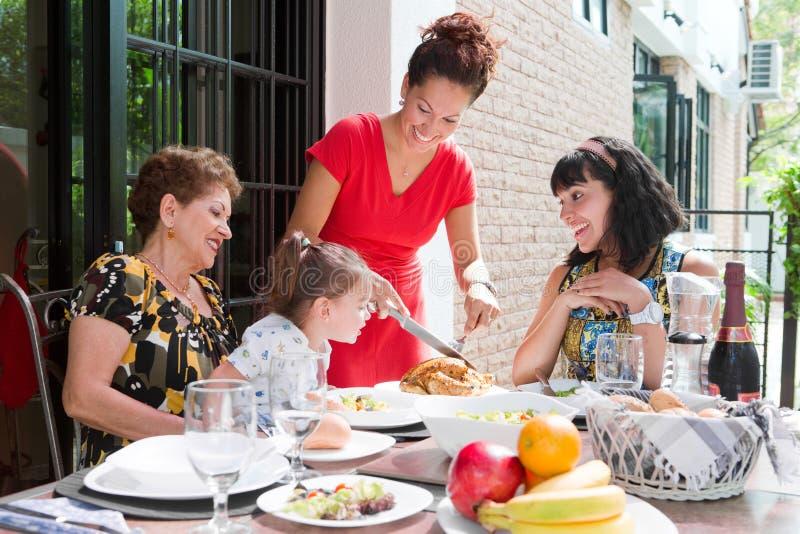 Schöne hispanische Familie, die zusammen eine Hauptmahlzeit im Freien genießt stockfoto