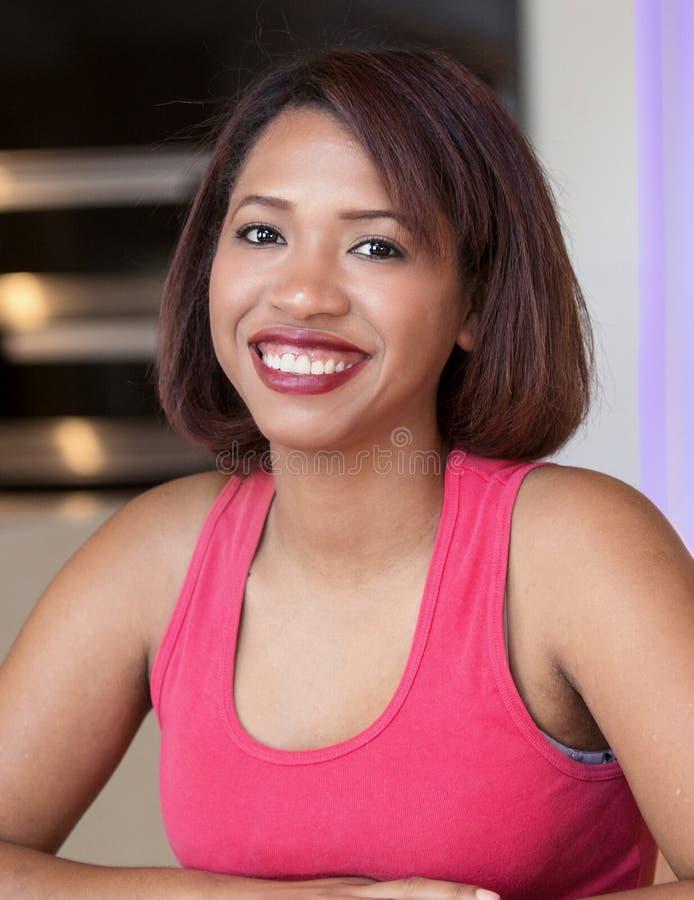 Schöne hispanische Frau, die an der Kamera lächelt lizenzfreies stockfoto