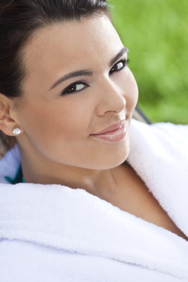 Schöne hispanische Frau im weißen Bademantel am Badekurort stockfotografie