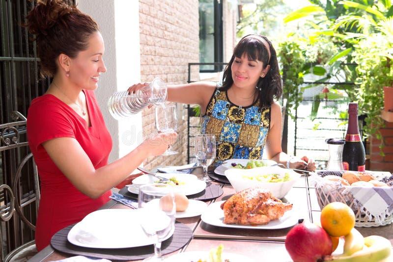 Schöne hispanische Frauen, die zusammen eine Hauptmahlzeit im Freien genießen lizenzfreies stockbild