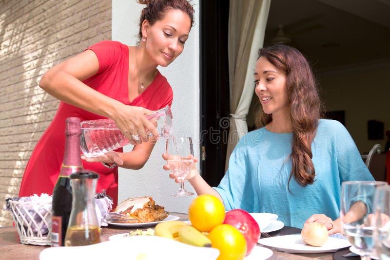 Schöne hispanische Frauen, die zusammen eine Hauptmahlzeit im Freien genießen stockbild