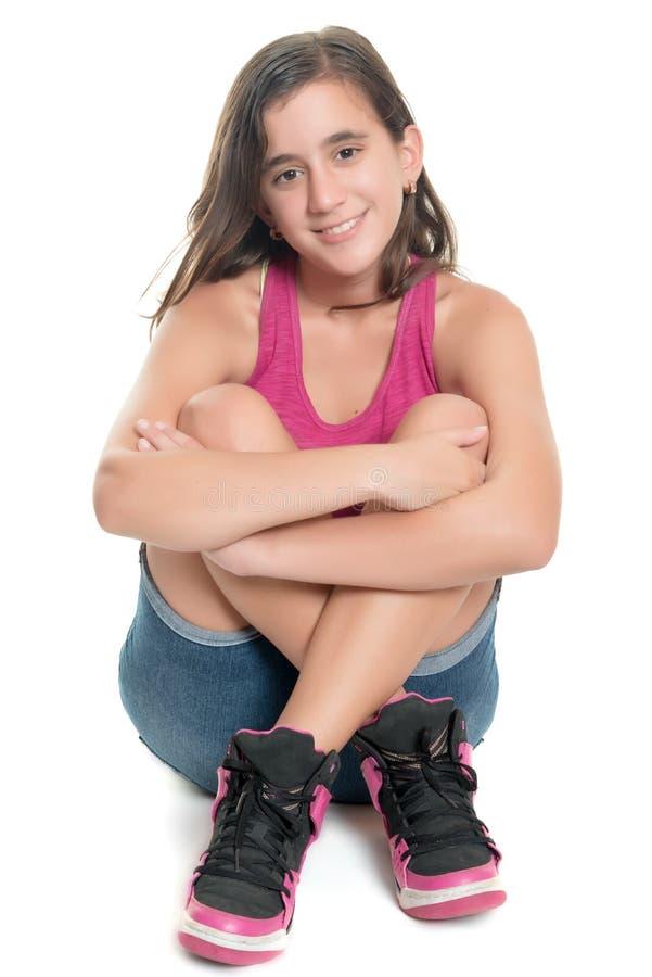 Schöne hispanische Jugendliche, die auf dem Boden und dem Lächeln sitzt stockfoto