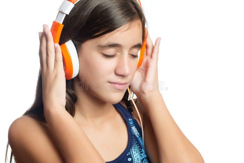 Schöne hispanische Jugendliche, die Musik auf Leuchtorangekopfhörern genießt lizenzfreies stockfoto