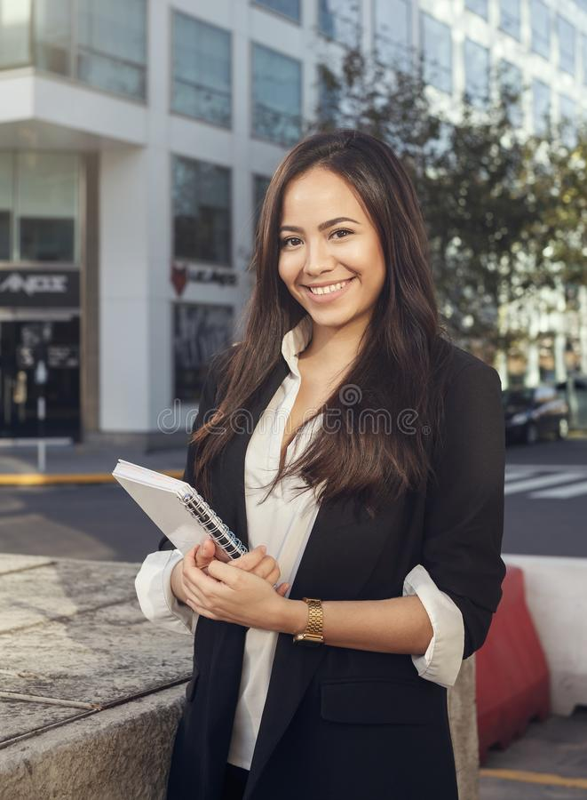 Schöne hispanische junge Geschäftsfrau, die an der Kamera lächelt lizenzfreie stockfotos