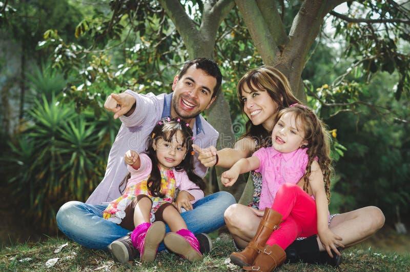 Schöne hispanische vierköpfige Familie, die draußen sitzt stockfotos