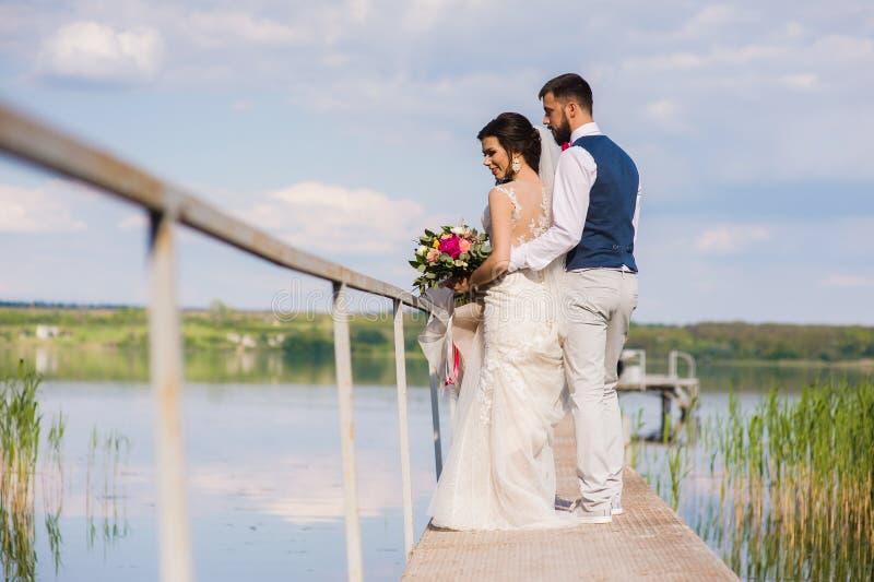Schöne Hochzeitspaare, die auf bringe umarmen stockfotos