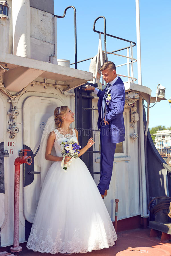 Schöne Hochzeitspaare, die auf dem Boot aufwerfen lizenzfreie stockfotos