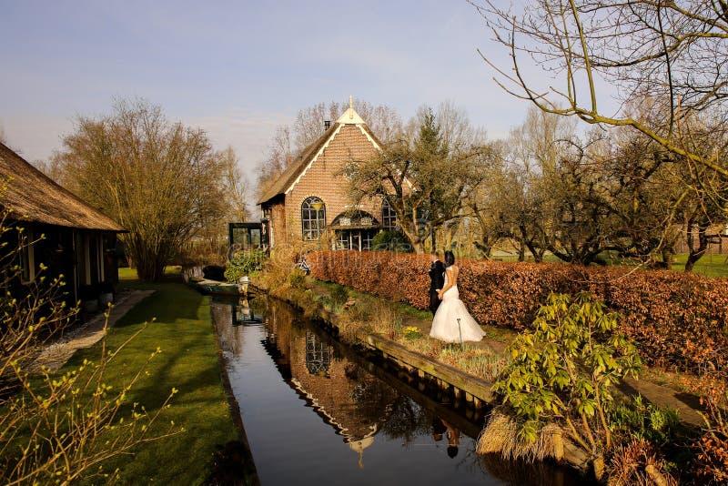 Schöne Hochzeitspaare, die nahe Fluss aufwerfen lizenzfreies stockbild