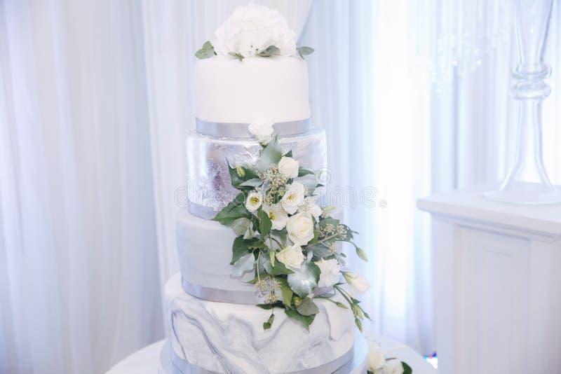 Schöne Hochzeitstorte verziert mit Blumen Silberne und weiße Farbe lizenzfreie stockbilder