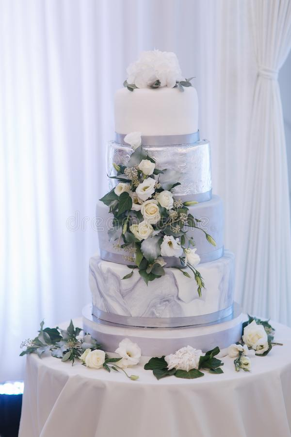 Schöne Hochzeitstorte verziert mit Blumen Silberne und weiße Farbe lizenzfreie stockfotografie