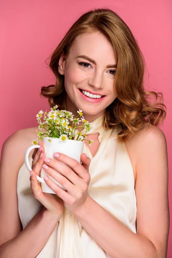 schöne Holdingschale der jungen Frau mit Kamille und Lächeln an der Kamera stockbilder