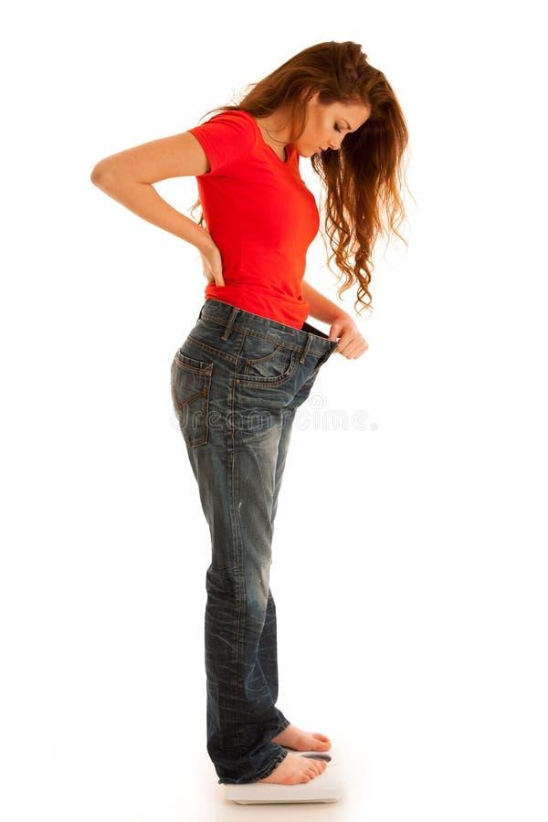 Schöne Holdingskala der jungen Frau und zu große Hose als sie lizenzfreie stockfotografie