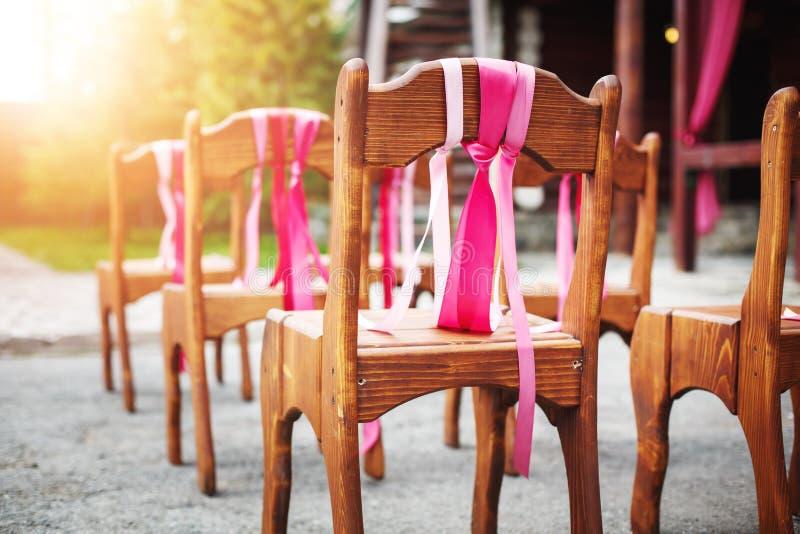 Schöne Holzstühle verziert mit Bändern lizenzfreie stockbilder