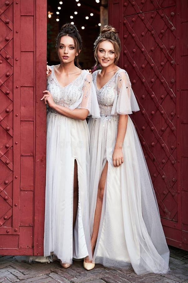 Schöne, im Retro-Stil gehaltene Bridesmaierinnen in wunderschönen eleganten, hellgrauen, silberfarbenen Kleider in alten Kleider lizenzfreies stockbild