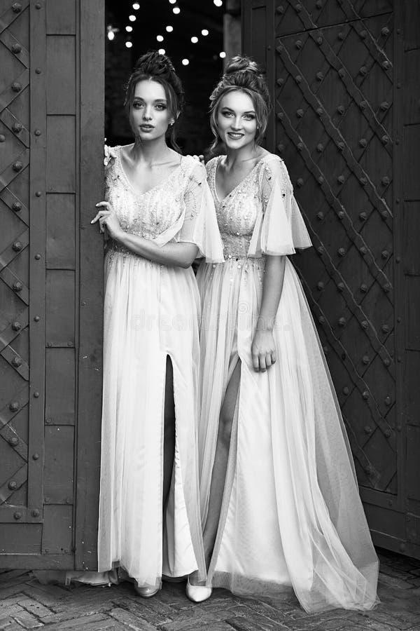 Schöne, im Retro-Stil gehaltene Bridesmaierinnen in wunderschönen eleganten, hellgrauen, silberfarbenen Kleider in alten Kleider lizenzfreie stockfotografie