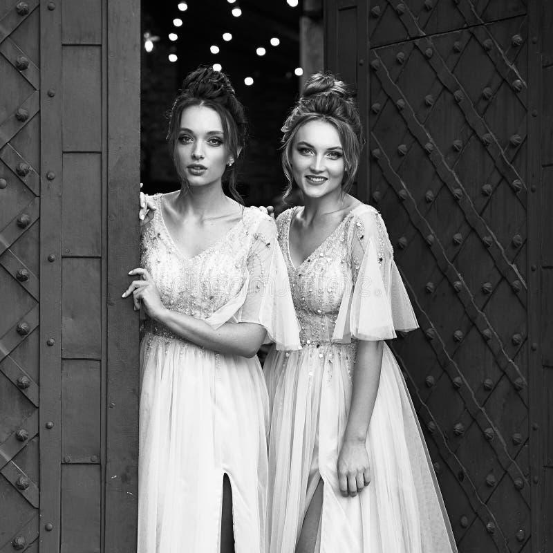 Schöne, im Retro-Stil gehaltene Bridesmaierinnen in wunderschönen eleganten, hellgrauen, silberfarbenen Kleider in alten Kleider lizenzfreies stockfoto
