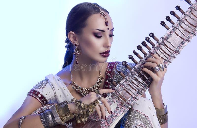 Schöne indische Frau im Sari mit dem orientalischen Schmuck-Spielen lizenzfreie stockfotos