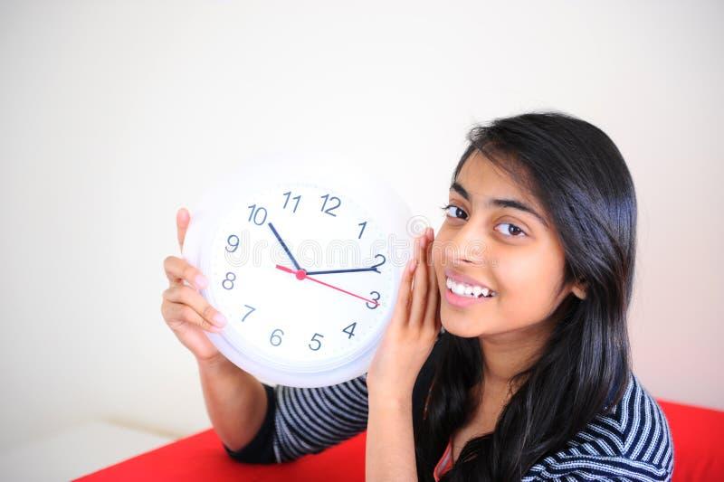 Schöne indische Mädchenholdingborduhr stockfotografie