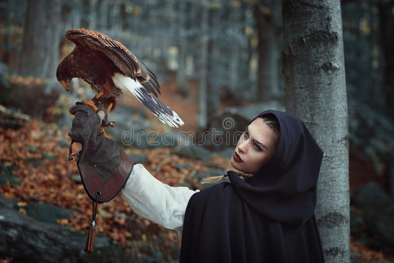 Schöne Jägerin mit Falken in einem Wald lizenzfreie stockfotos