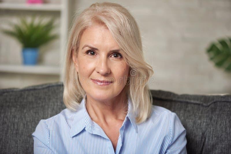 Schöne 50 Jahre Frau sitzt auf einem Sofa zu Hause lizenzfreie stockfotografie